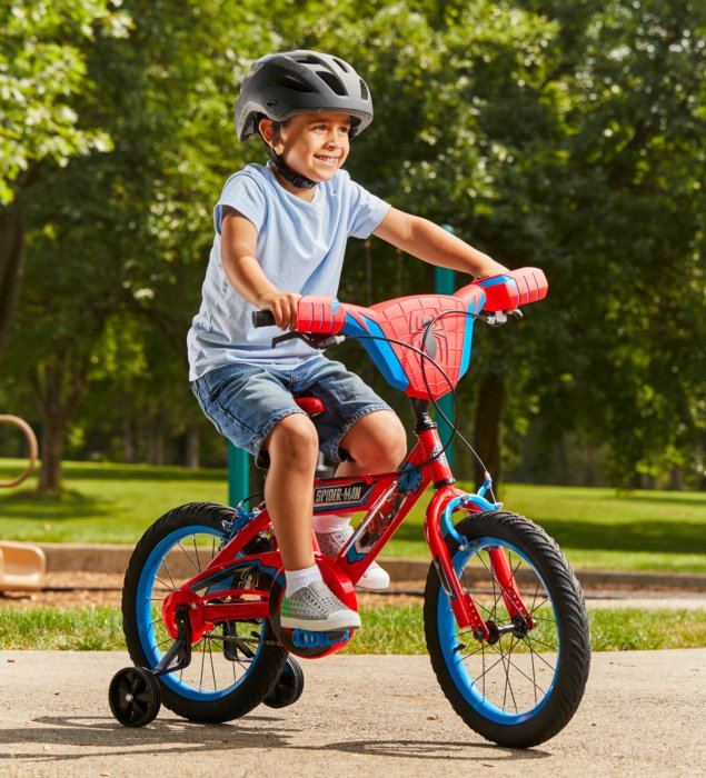 A young boy riding on a spiderman bike with training wheels