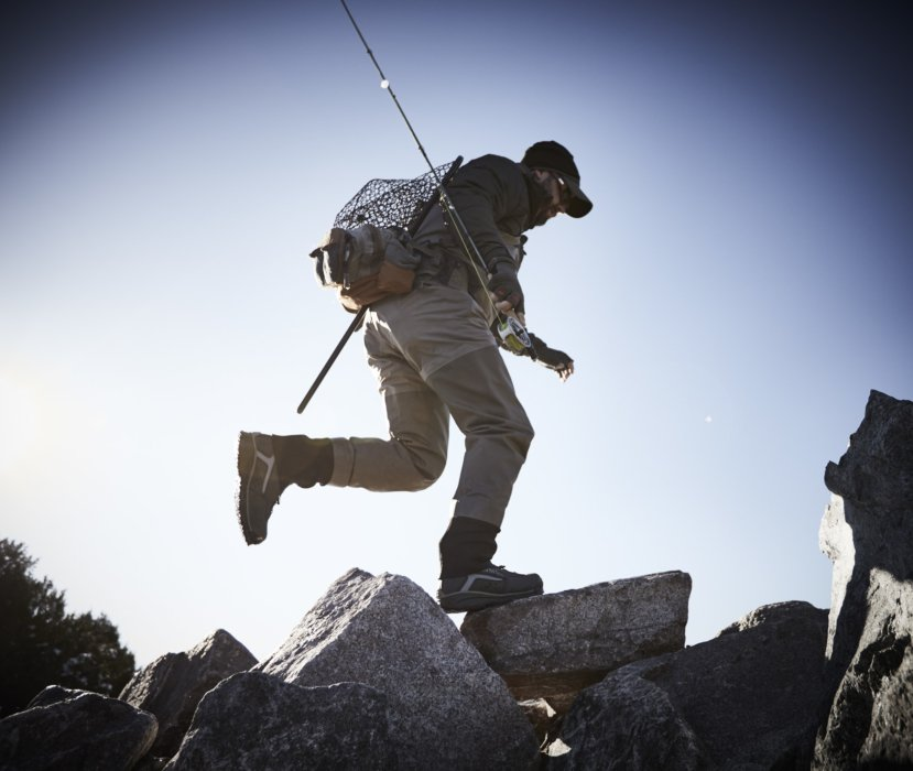 a fly fisherman running on rocks