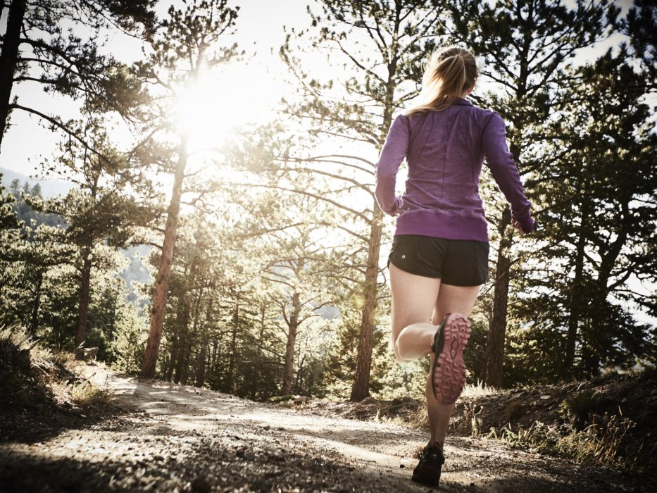 Athlete woman running in the woods