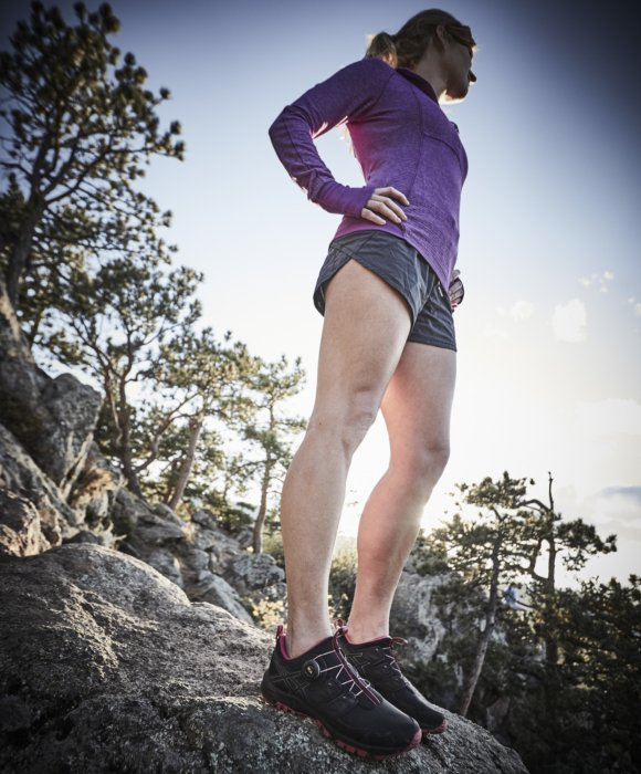 A young athletic woman standing on a rocky terrain