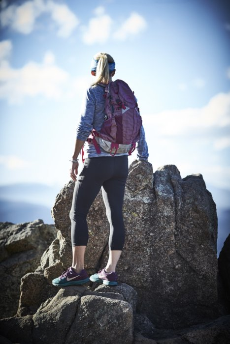 A young athlete woman with backpack near the top of mountain peak