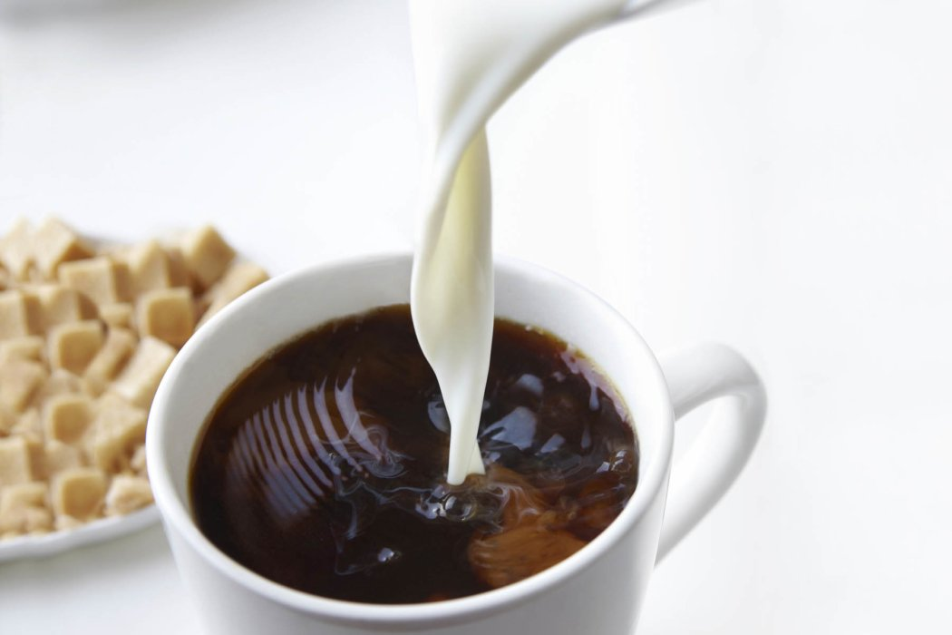 Cream pouring into hot coffee