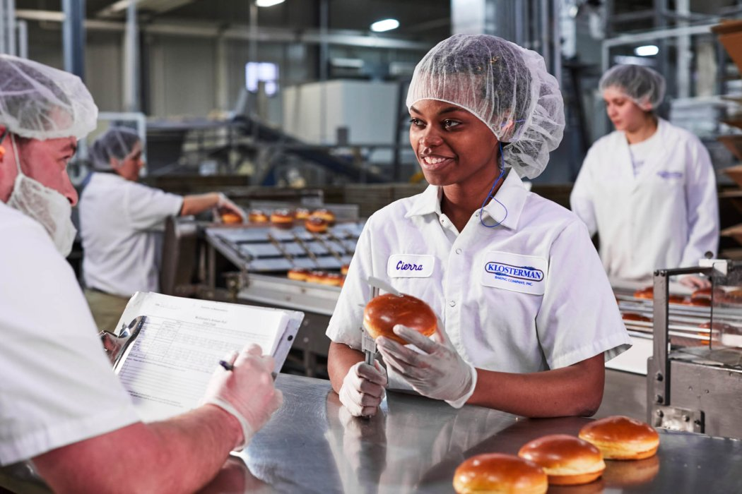 A line worker in a factory inspecting baked good such as buns