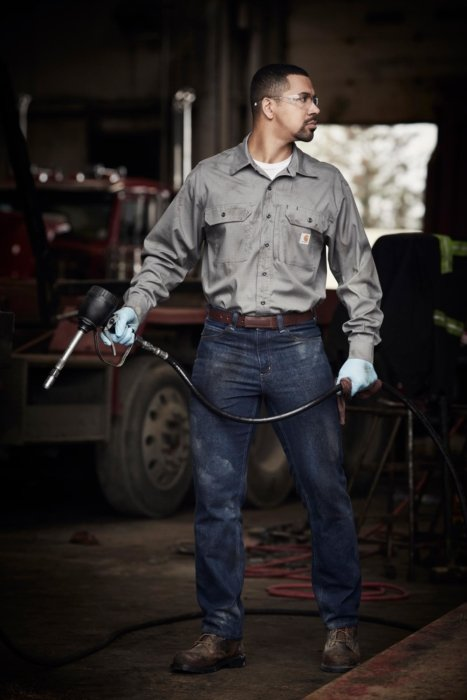 Man working in a garage with industrial clothes