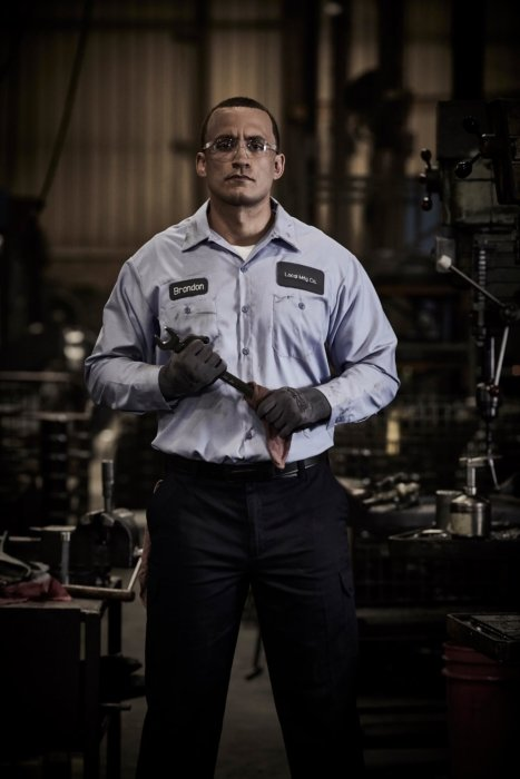 A model holding a wrench in an industrial environment wearing professional work clothes