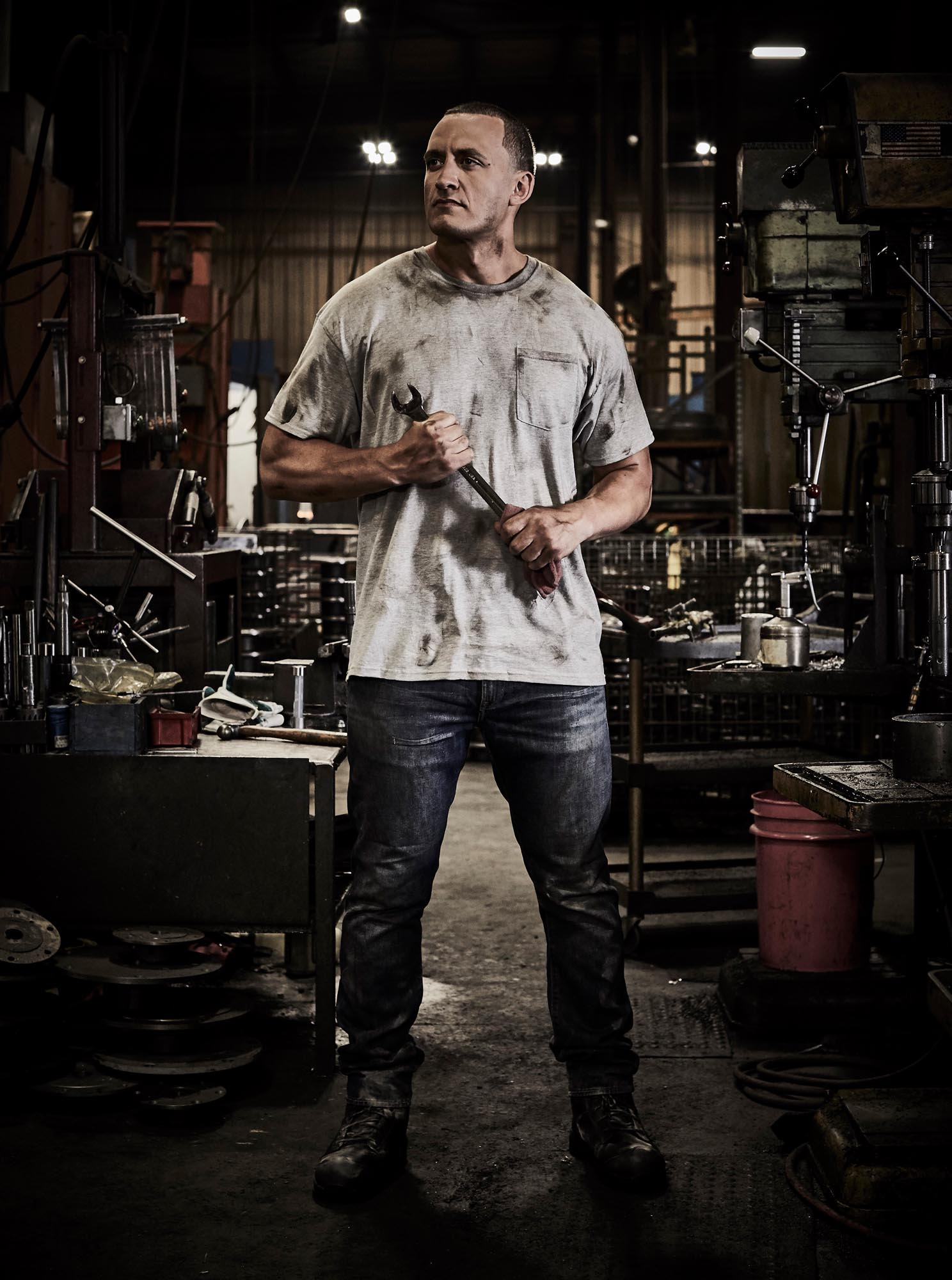A model holding a wrench in an industrial environment