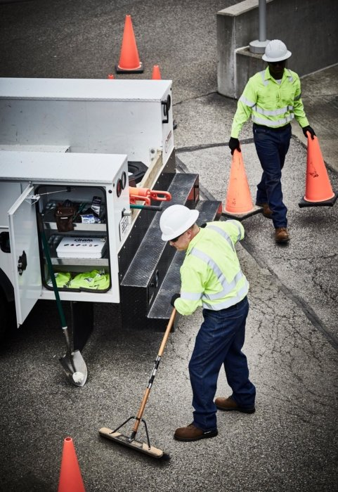 Two men working on cleaning up a job site near truck - work photography