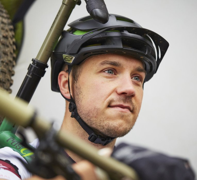 Portrait of a young cyclist carrying his bike