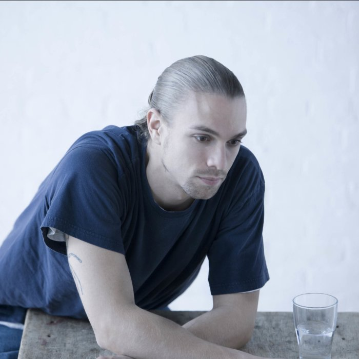 Serious portrait of a young man leaning on a table