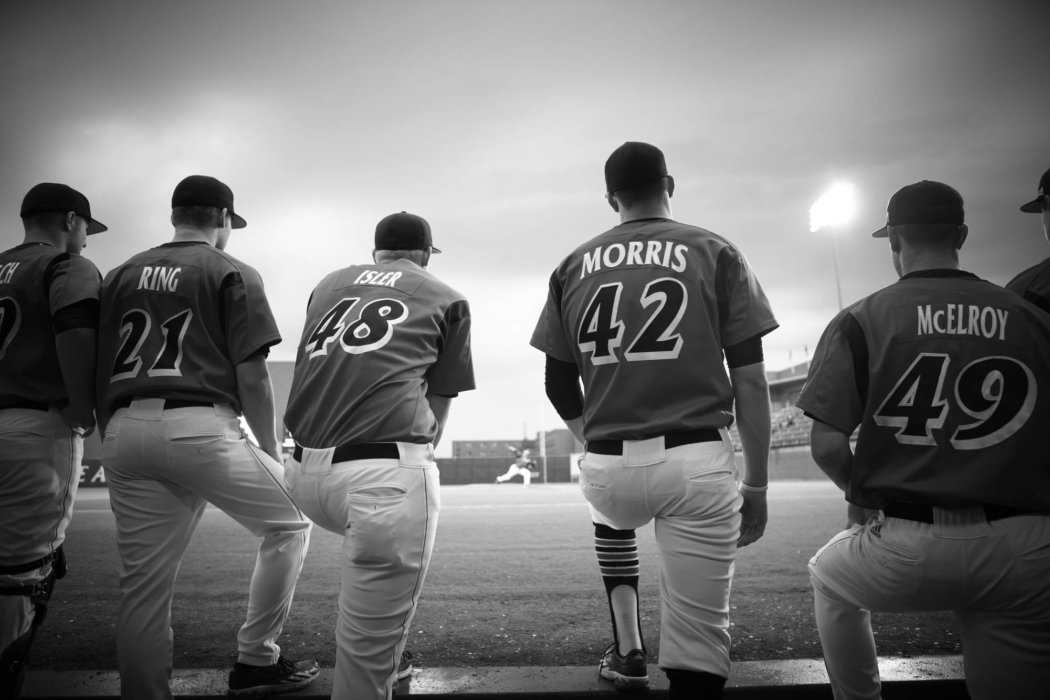 A group of baseball players kneeling for the national anthem