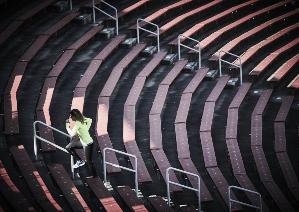 A young female runner training up red stadium steps