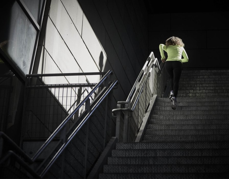 A young athlete woman running up modern steps