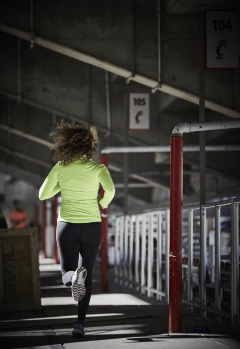A young athlete female running under a stadium