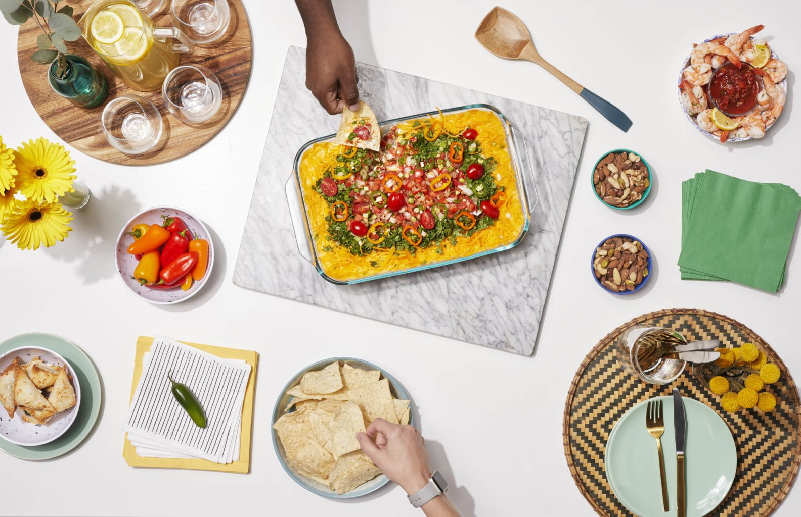 A spread of nacho dips and snacks with pyrex dished. Bold and modern