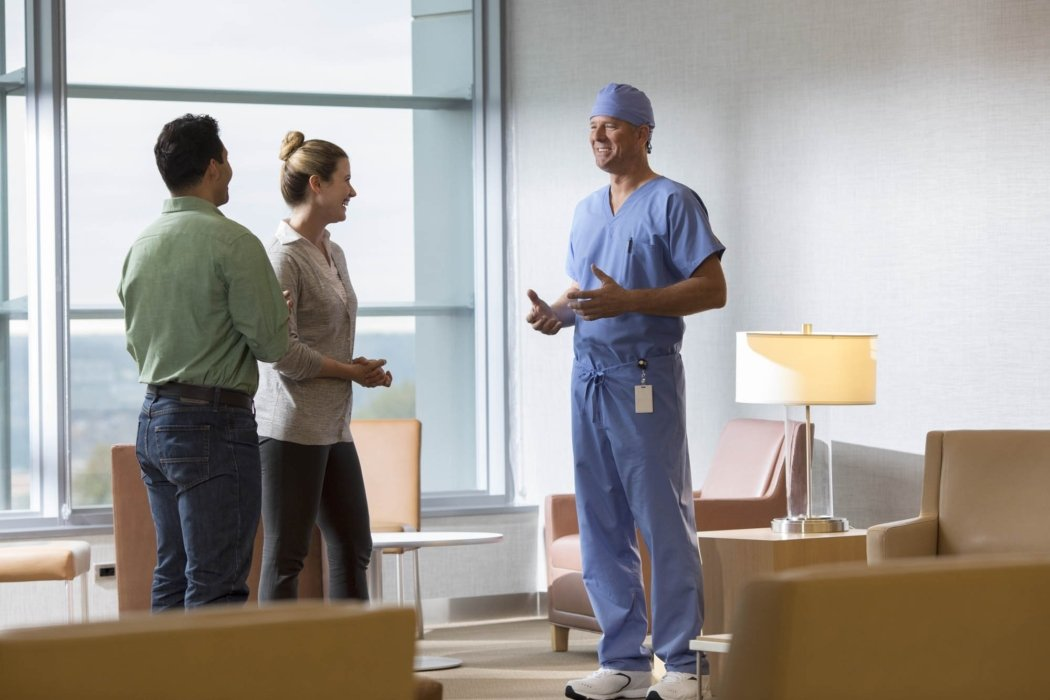A doctor in scrubs talking to family members in a waiting room | Healthcare Photographer