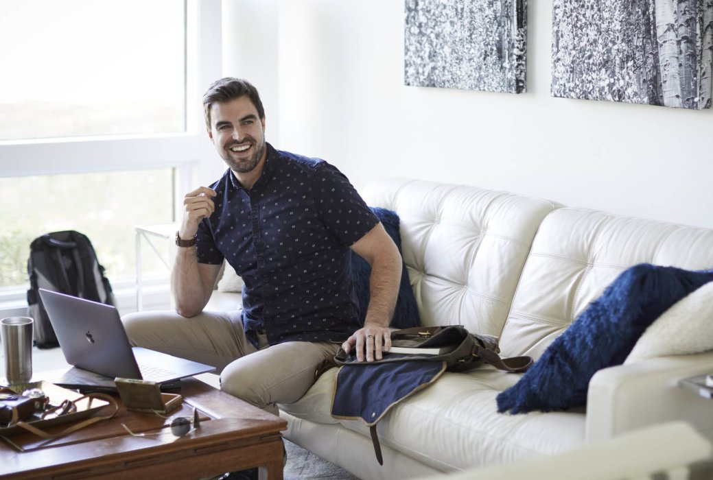 Lifestyle of a man working at home on couch with laptop - lifestyle photography