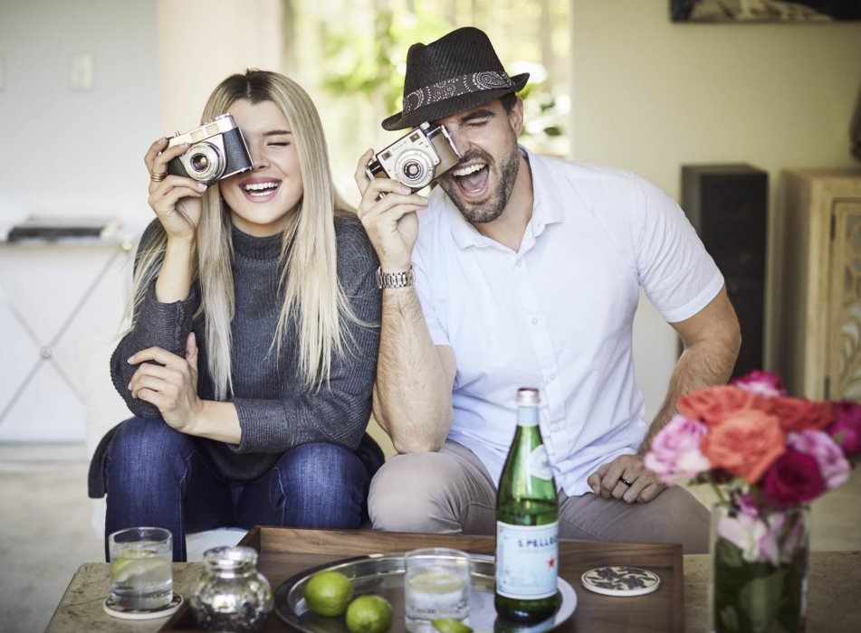 Lifestyle of couple playing with cameras and having some drinks - lifestyle photography