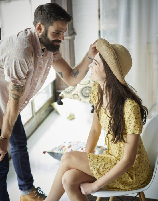 A couple having a cute moment while wearing straw hat
