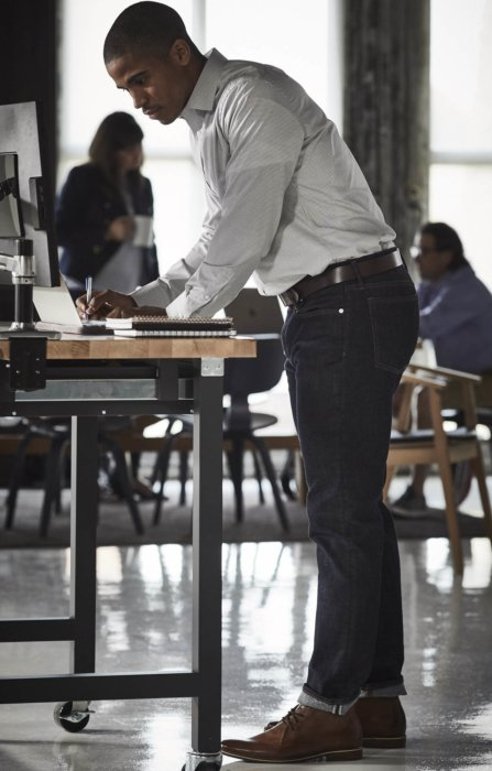 Lifestyle of man working at desk in an open office