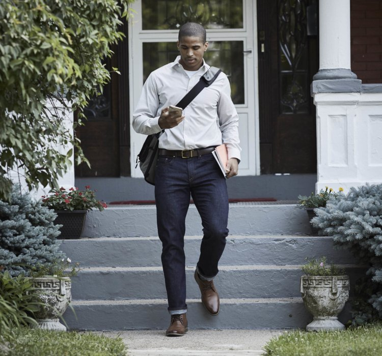 Lifestyle of a young business man stepping out the door - lifestyle photography
