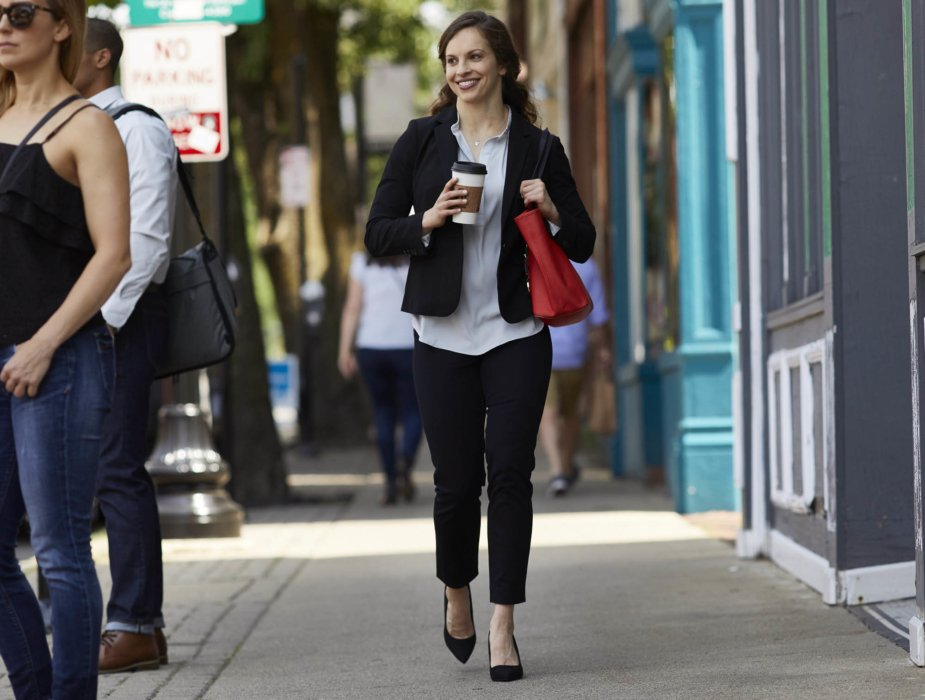 Lifestyle of young businesswoman waling down a city street