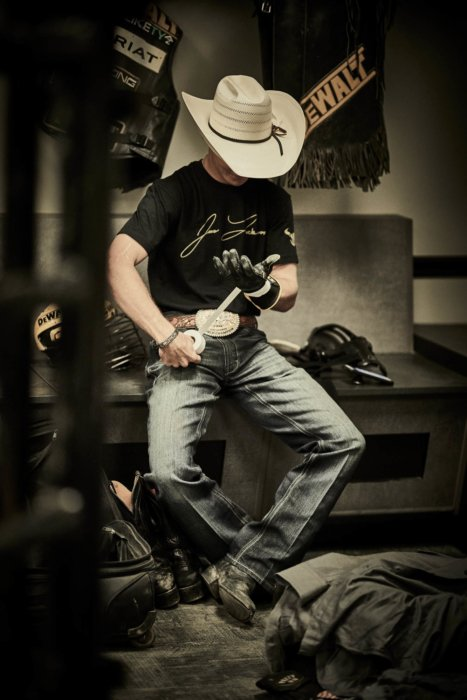 A bull rider at PBR getting on his clothes - apparel photography