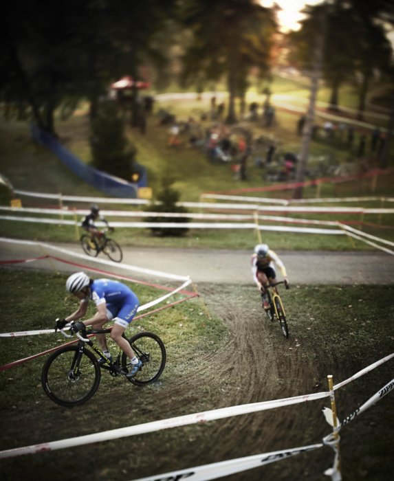 Three Cyclocross riders racing up a muddy switchback