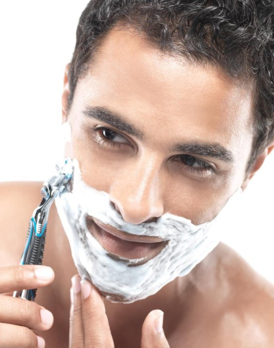 Beauty shot of a young man shaving his face
