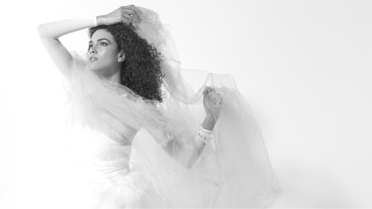 A fashion model wearing white sheer dress looking up