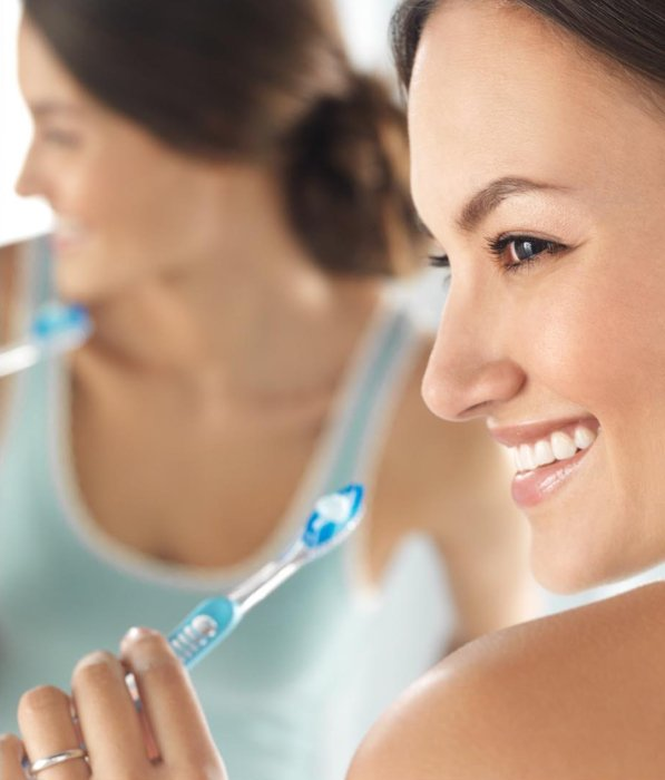 Beauty shot of a young woman brushing her teeth