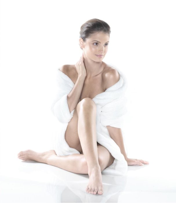 Beauty shot of a woman featuring her legs in a white robe