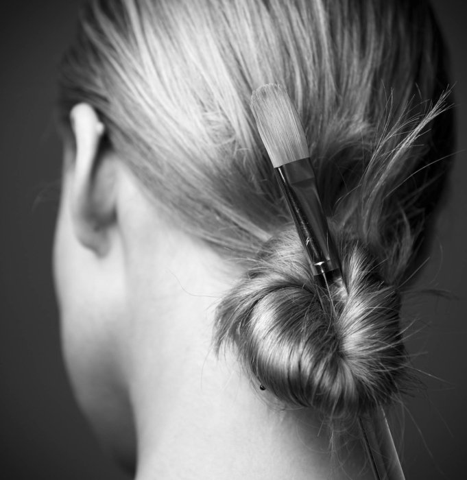Beauty shot a woman's hair with paint brush in a bun