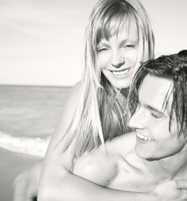 A beauty shot of a young couple at a beach holding each other