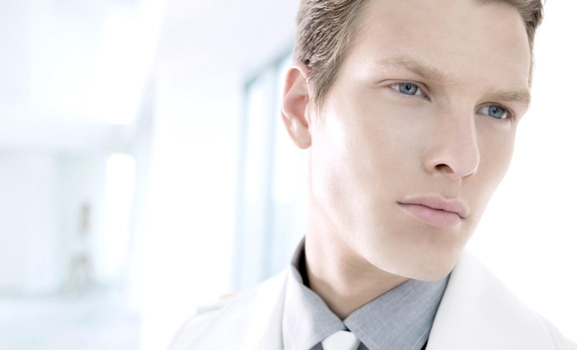 A young fashion male model in a white modern setting and white suit