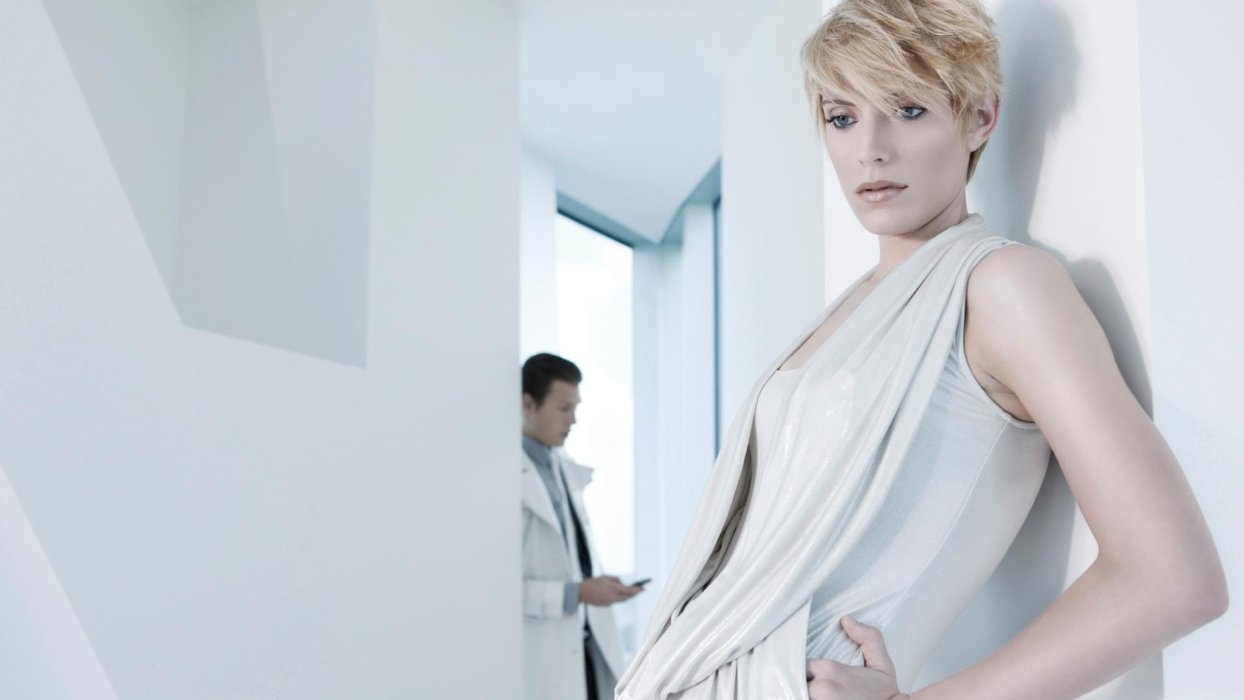 A fashion model wearing white sheer clothes leaning against a wall