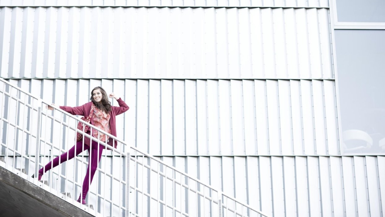 A fashion modern walking happily down some industrial steps