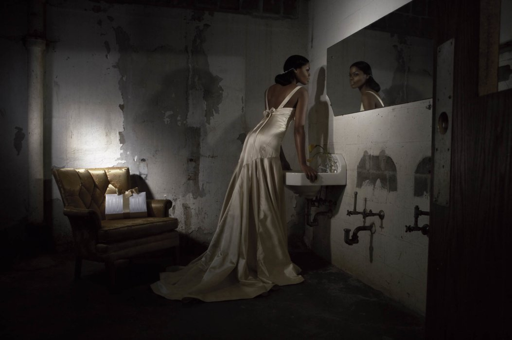 A fashion model wearing a wedding dress in a dark setting