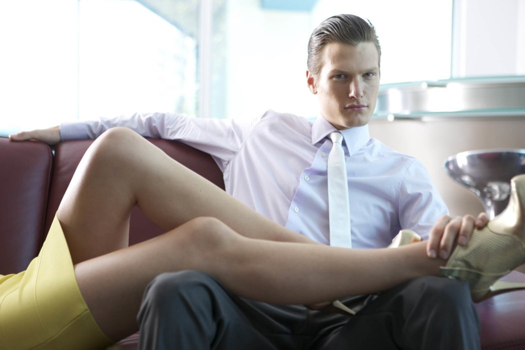 A fashion model wearing sharp business clothes with a woman's legs on his lap