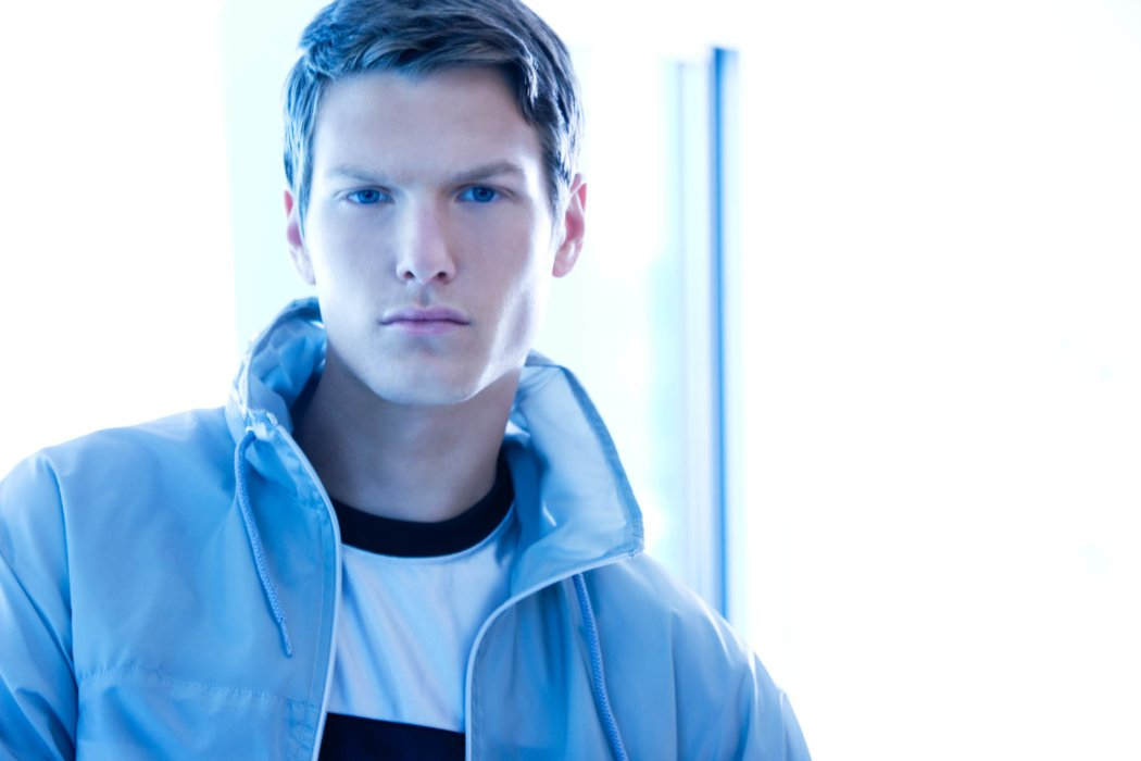 A fashion model wearing blue clothes with bright futuristic lighting