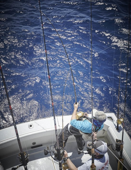 Two deep sea fisherman with reeling in a catch