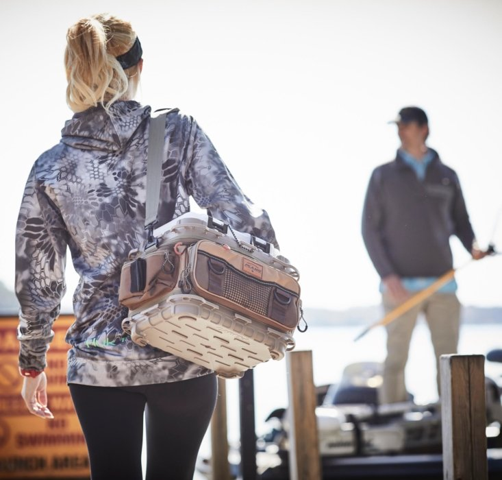 A fishing girl walking on a dock with a Plano tackle bag