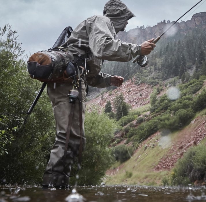Man in a river fly fishing in the rain - apparel photography