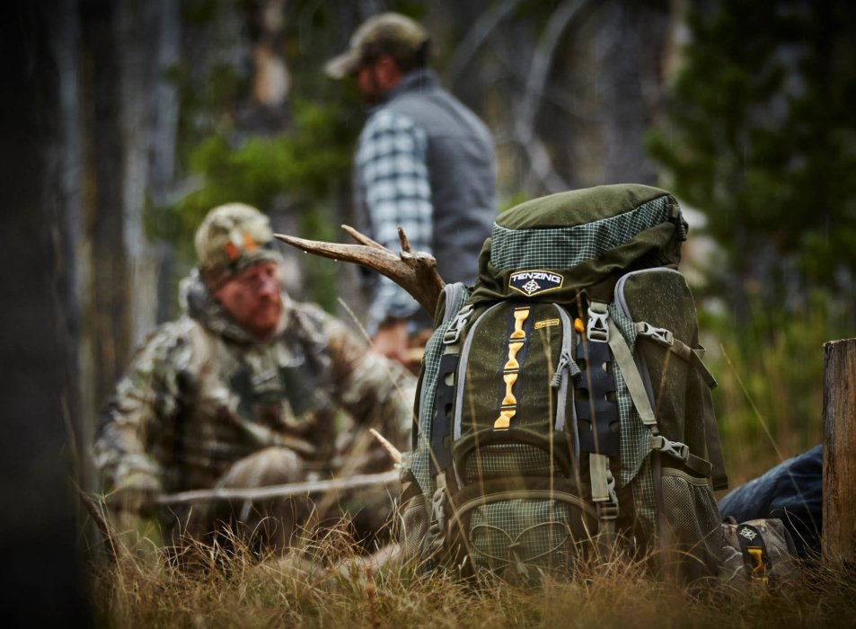 A tenzing back pack with deer antlers near a few hunters