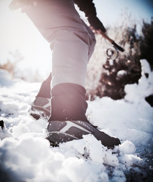 Fly fisherman's shoes trekking up a snowy hill