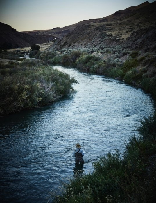 A fly fisherman wading in a stream