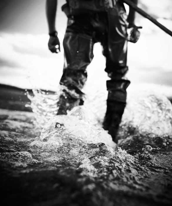 A dramatic shot of a fisherman splashing in a stream