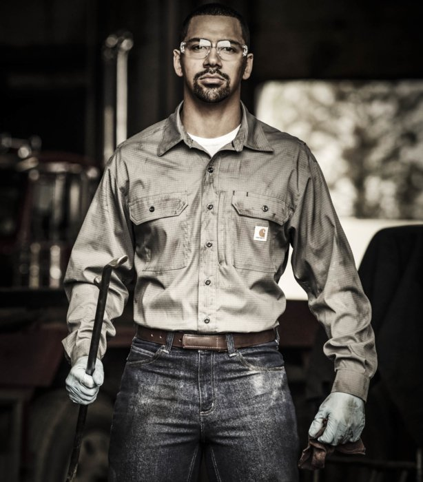 A man in work apparel looking with crowbar