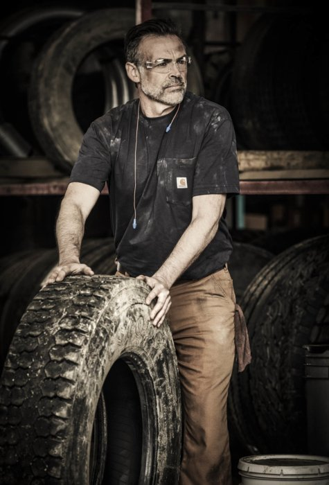 A man in a dirty work environment pushing a large tire
