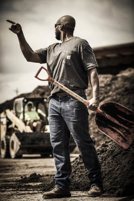 A man working at a landscaping facility holding a large shovel