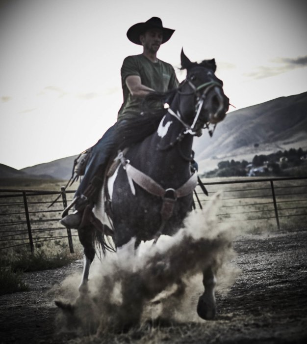 A rancher riding a horse kicking up dirt